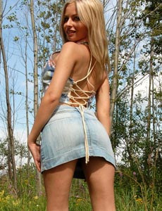 Blonde beauty in jeans skirt is smoking in the forest nude with puffy nipples