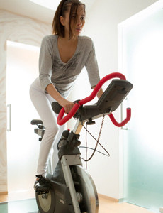 Exciting young brunette is on the exercise bicycle in tight top and white spandex