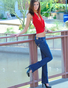 Wonderful young baby in tight blue jeans undresses outdoor