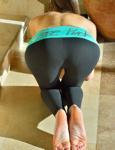 Amazing girl with perfect body shapes in stretching for yoga in tight black pants