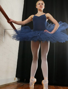 Sexy ballerina in tight outfit with the legs covered with white nylon does exciting flexible poses before strips