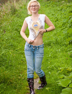 Sexy blonde hottie in blue jeans and under umbrella walking nude outside