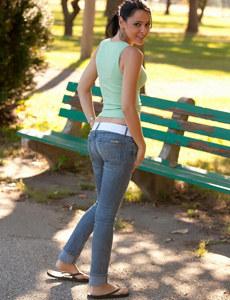Sexy brunette baby is in the park on the bench dressed in tight blue jeans and green top
